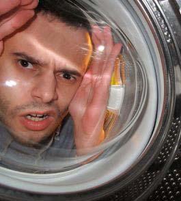 Мужчина смотрит внутрь бака стиральной машины